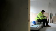 Construction Worker Using a Mobile Telephone on his Lunch Break video