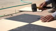 construction worker using hammer tiling floor video