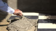 construction worker using putty knife tiling floor video