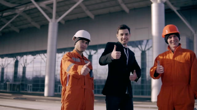 Construction workers and their manager showing thumbs up. The builder, master, worker showing thumbs up. video
