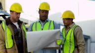 Construction workers look over plans and discuss video