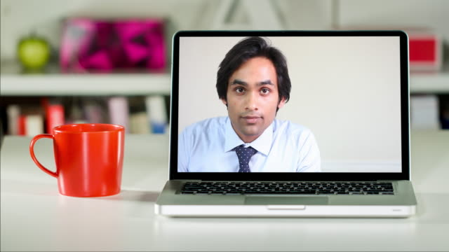 Consultant listening to an off-camera client on a laptop computer video