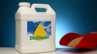 Container of Biodiesel fuel sits next to soybeans video