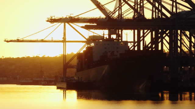Container Ship in Shimmering Port Channel at Sunset video