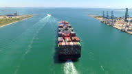 AERIAL: Container ship, loaded with shipping freight containers leaving port, freight transportation video