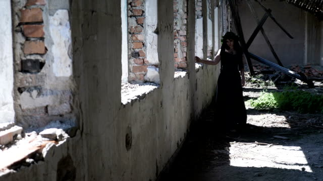 Contemplative gothic witch girl walking beside ruined windows in an old destroyed mansion video