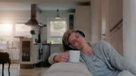 Contented woman relaxing listening to music video