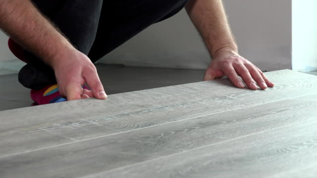 Contractor installing wooden laminate flooring with insulation video