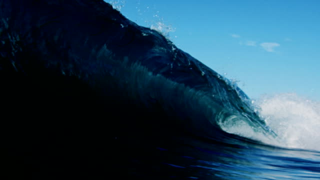 Contrasting of huge beautiful wave breaking of the camera with the clear summer sky of California. Shot in slowmo on the Red Dragon at 300FPS. video