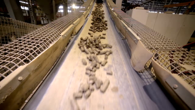 Conveyor with soil. Clay goes through transporter in a mining factory video