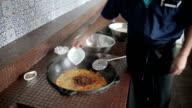 Cook adding spices into the pot. video