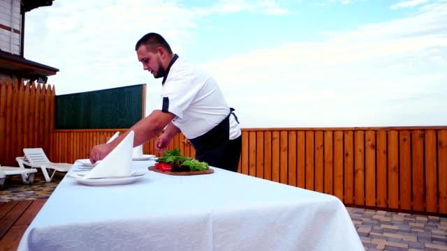 Cook at home, Professional chef serves a table on the terrace, a table covered with a white tablecloth and napkins video