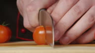 CLOSE UP: A cook cuts a cherry tomatoes on a cutting board in a kitchen video