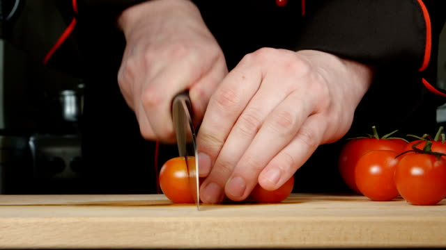 Cook cuts a cherry tomatoes on a cutting board video
