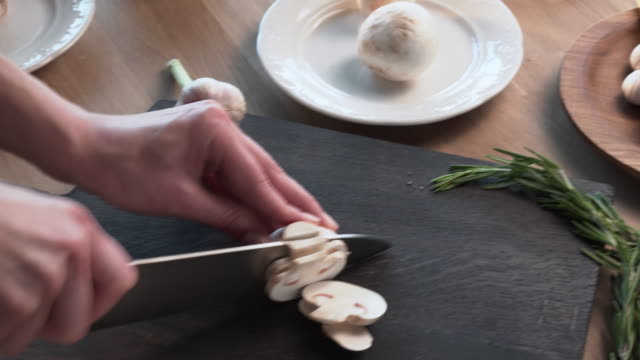 cook cuts mushrooms with a sharp knife video