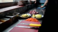 Cook cuts the vegetables on the kitchen table. video