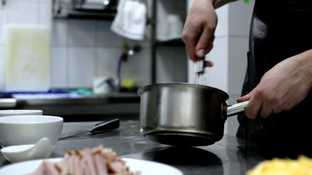 Cook hands whipping cream and eggs in a pan video