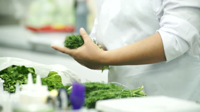 Cook in a white apron, choose a good dill and gathers in her hand video