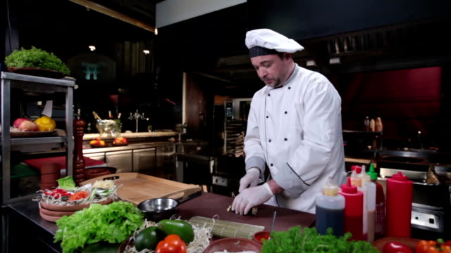 Cook in white uniform making sushi rolls, restaurant kitchen video