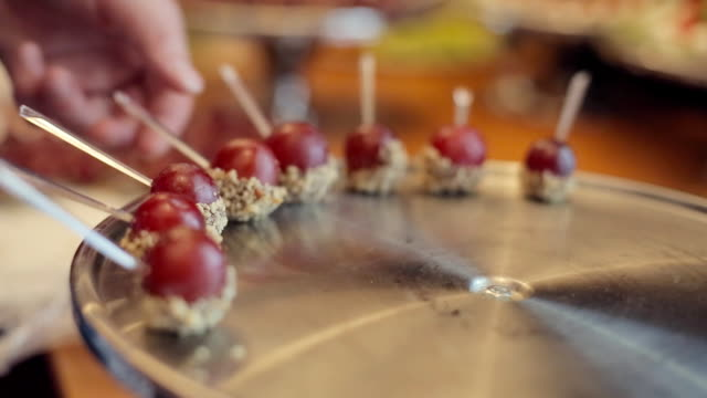 Cook lays grapes in nuts and chocolate on a tray video