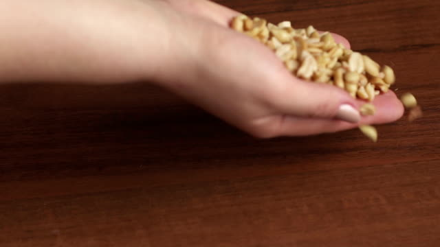 Cook pours peanut nuts on the table, close-up. video