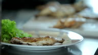 Cook puts chopped fried chicken on the plate video