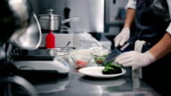 Cook puts lettuce on a white flat dish. video