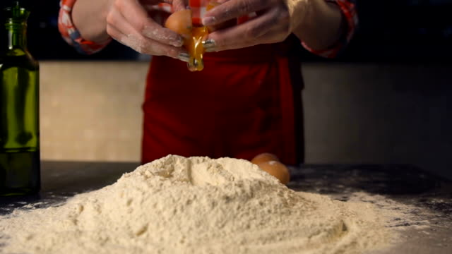 Cook throw an egg on a pile of flour .In the kitchen of a pizzeria video
