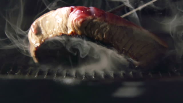SLOW: A cook turns up a steak of meat on a grill video