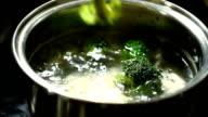 cooked broccoli pieces closeup over a saucepan video