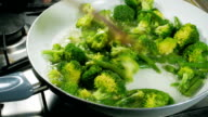 Cooking broccoli and green beans in a frying pan. Stirring with a wooden spoon. video