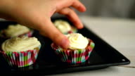 Cooking cupcakes. Hand put cup cake on baking tray. Homemade cupcakes video