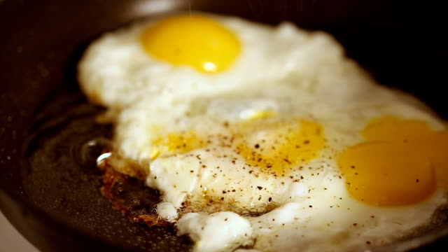 Cooking fried eggs with spice in frying pan for breakfast video