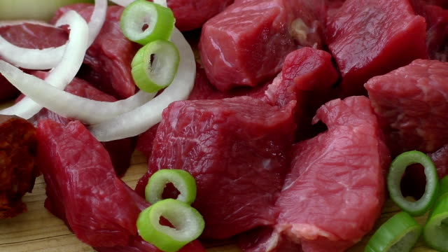 Cooking goulash with beef meat and vegetables. Fresh raw meat on cutting board video