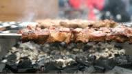 Cooking of pig meat on the metal skewers on coals video
