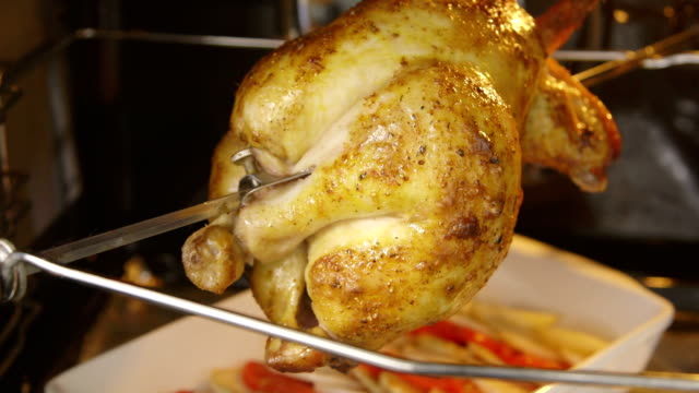 Cooking oven roasted rotisserie whole chicken closeup video