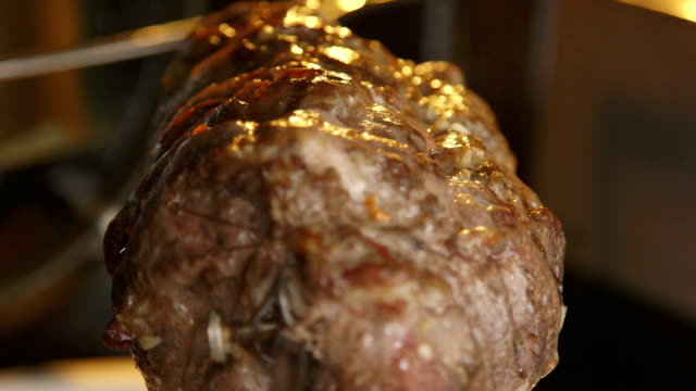 Cooking rotisserie pork roast in hot oven closeup video