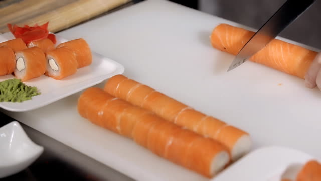 cooking sushi rolls. cutting into portions, Philadelphia roll of rice, salmon, cream cheese video