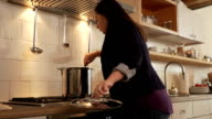 Cooking time. Women enters the kitchen and checks on soup video