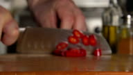 SLOW: A cook's hand cuts a chili pepper by a knife video