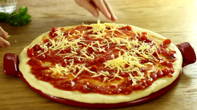 Cook's hand putting cheese on the pizza video
