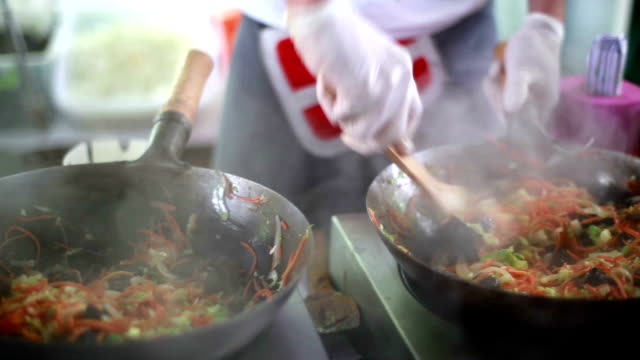 Cooks prepare Chinese noodles with vegetables on a street video