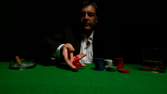 Cool gambler throwing red dice video