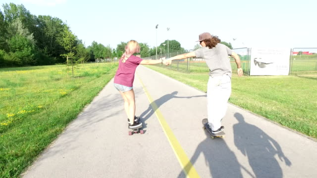 Cool man passing with skate under the arms of other two skateboarders video