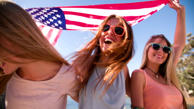 Cool teen friends smiling and holding an American flag video