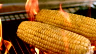 Corn being cooked on flaming barbecue video