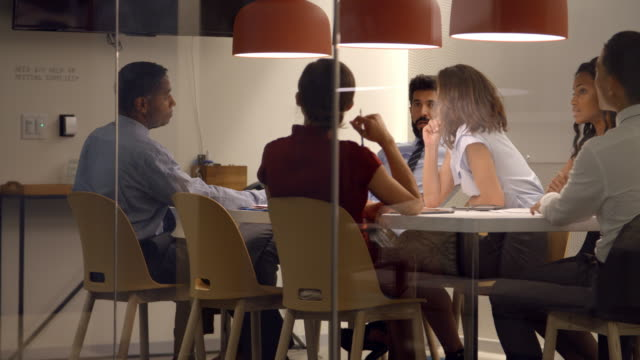 Corporate team at table in a meeting room cubicle, close up video