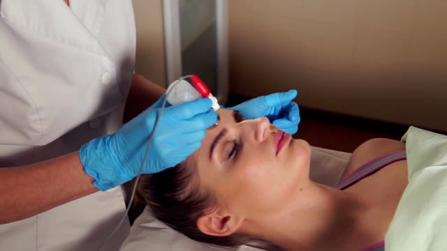 Cosmetologist preparing woman's face for a non-injection mesotherapy treatment. video