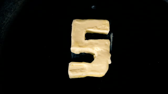 Countdown animation of butter in shape of numbers melting on hot pan - Close up top view video