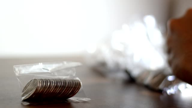 Counting coins into plastic bag video